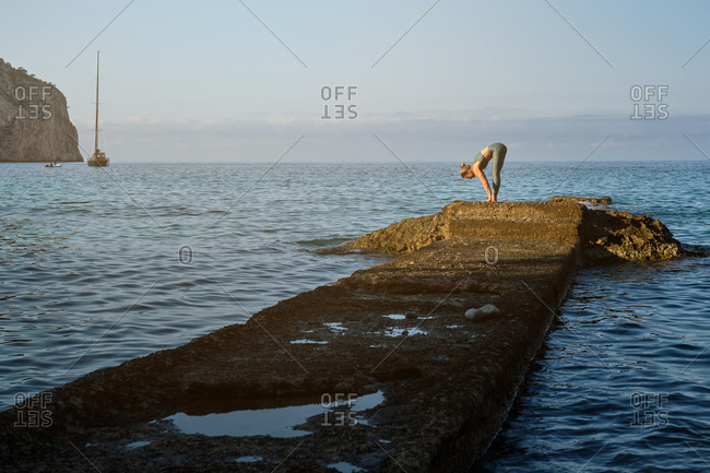 Full body side view of unrecognizable female in sportswear doing Standing Forward Bend while practicing yoga alone on rocky pier at seaside