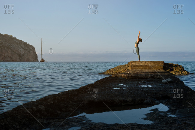 Full body side view of distant slim female in sportswear standing in Mountain pose with arms up while practicing yoga on seashore