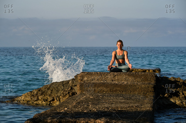 Peaceful female sitting on stone in Padmasana and meditating with mudra gesture near sea during sundown
