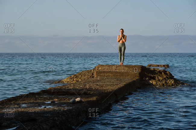 Calm female in sportswear practicing yoga in Tadasana with Namaste hands while standing on rock on background of seascape in summer
