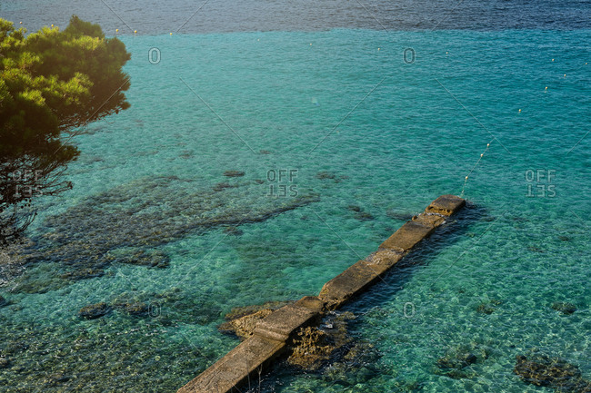 Picturesque view of turquoise sea water and stone pier against blue cloudless sky