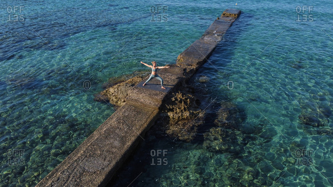 Low angle of peaceful female standing on pier near sea and practicing yoga in Virabhadrasana while looking away