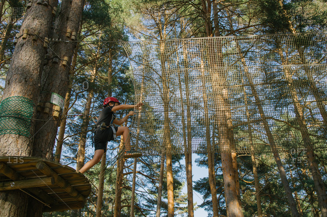 Low angle side view of brave kid in helmet and protective harness walking along suspension net while spending weekend in adventure park in forest