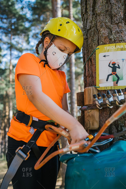 Focused girl in protective mask and helmet standing near tree in adventure park and putting carabine on safety rope during coronavirus