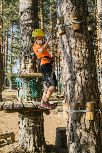 Concentrated kid in medical mask and safety equipment standing on wooden suspension bridge in adventure park during COVID 19 epidemic