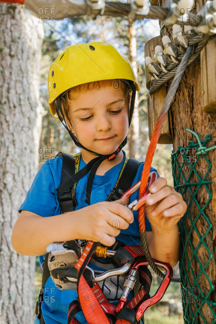 Adorable child in protective helmet and safety harness putting carabine on rope while spending weekend in adventure park in summer