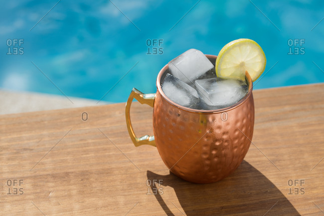 High angle of traditional Moscow mule alcohol cocktail with ice cubes and lime served in copper cup placed near pool