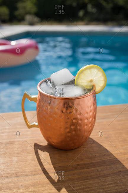 Traditional Moscow mule alcohol cocktail with ice cubes and lime served in copper cup placed near pool