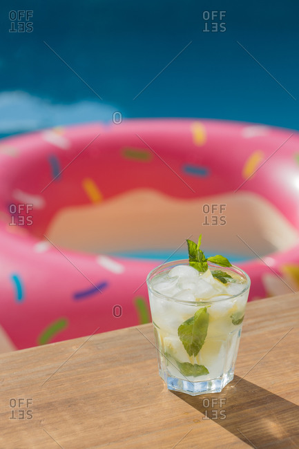 Refreshing Mojito cocktail with fresh lemon and mint leaves with ice cubes placed on wooden board near swimming pool in summer day