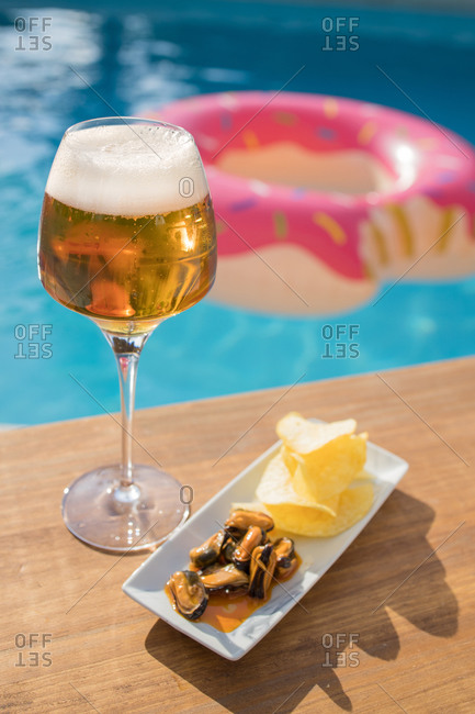 Fresh cold beer in goblet served with mussels and lemon on wooden counter against swimming pool in summer day