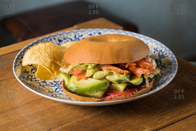Tasty salmon bagel with tomato tartar and pickles placed on wooden table in kitchen