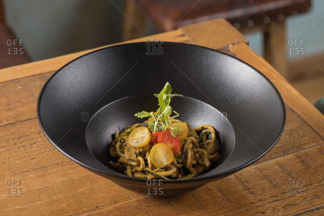 Bowl of tasty noodles with zucchini garnished with pesto sauce and cherry tomatoes placed on table in kitchen
