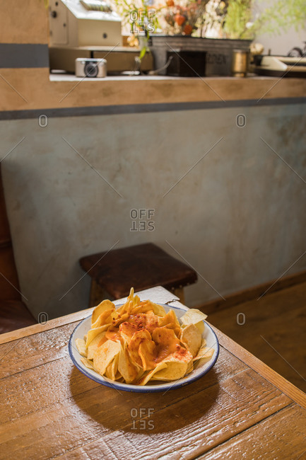 High angle of pile of crispy potato chips in bowl placed on wooden table at home