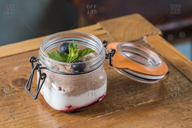 Closeup of glass jar with delicious chocolate mousse garnished with blueberries and sprig of mint and placed on wooden table in cafe