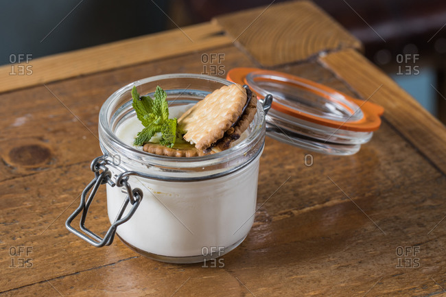Closeup of palatable cheesecake in glass jar garnished with chocolate chip cookie and sprig of mint