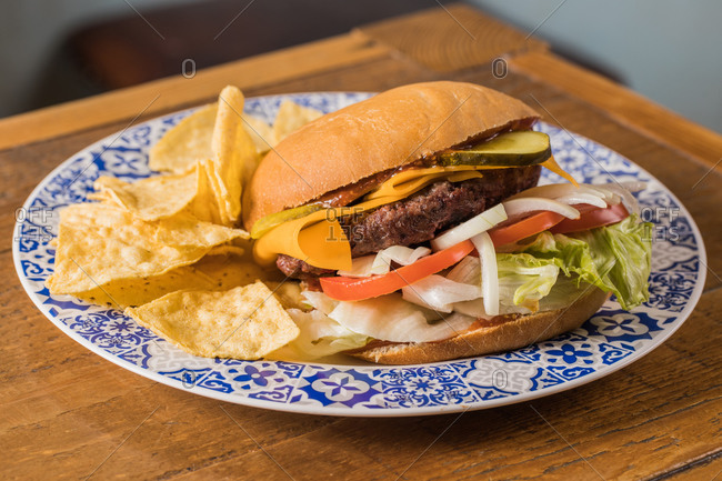 Closeup of appetizing burger with cheddar cheese and various vegetables on plate placed on wooden table in kitchen