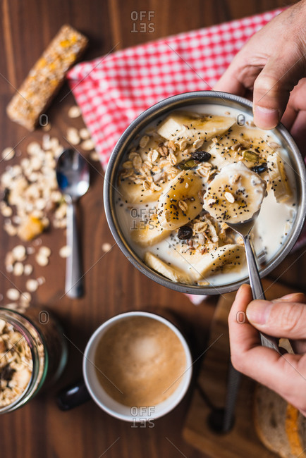 From above of crop anonymous person holding bowl with appetizing healthy breakfast made with yogurt and banana slices with oatmeal and seeds