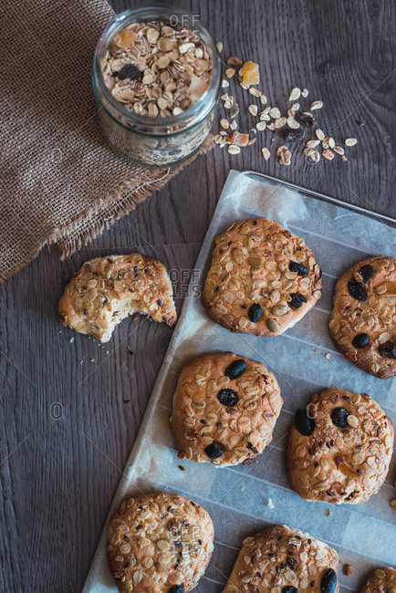Yummy crunchy freshly baked oatmeal cookies on baking paper placed on table during breakfast