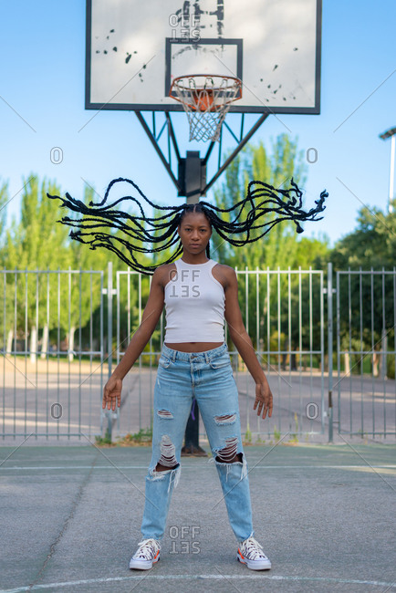 Full body young African American female in trendy ripped jeans and white top with waving braids standing against basketball hoop in urban park