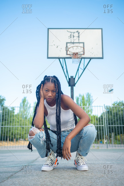 Full length of young African American female with braids wearing trendy ripped jeans and white tank top with sneakers sitting against basketball hoop on playground and looking at camera