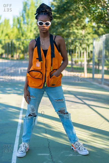 Full body modern young black female in trendy sunglasses dressed in bright orange vest and ripped jeans with sneakers standing in summer park
