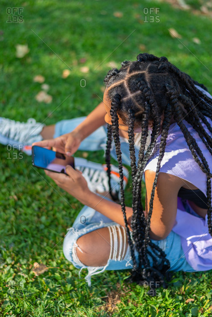 High angle side view of modern hipster African American female with Afro pigtails sitting on green grass and browsing smartphone while resting in park in summer day