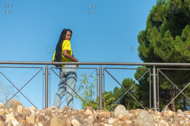 From below side view of confident young African American female hipster in colorful t shirt and jeans standing near banister in summer park and looking at camera