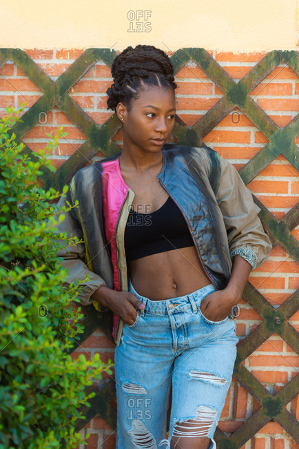 Stylish African American female teenager in trendy ripped jeans and jacket standing against brick wall on street and looking away
