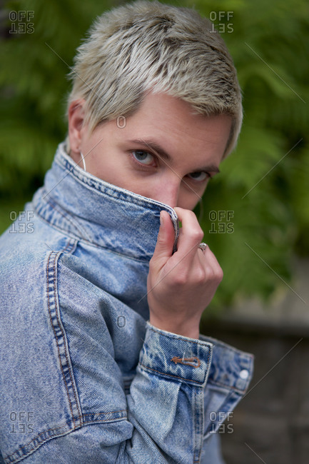 Side view of confident female in trendy outfit standing on street and covering face with denim jacket while looking at camera