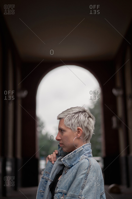 Side view of calm female model wearing denim jacket standing in arched passage on street and looking away