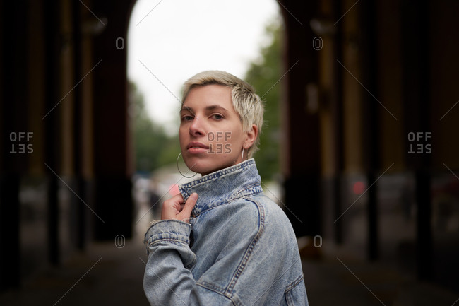 Side view of calm female model wearing denim jacket standing in arched passage on street and looking at camera