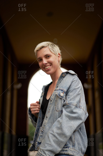 From below happy calm female model wearing denim jacket standing in arched passage on street and looking at camera