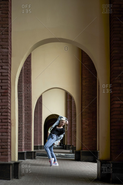 Talented female dancer in denim clothes performing in arched walkway in city and looking at camera