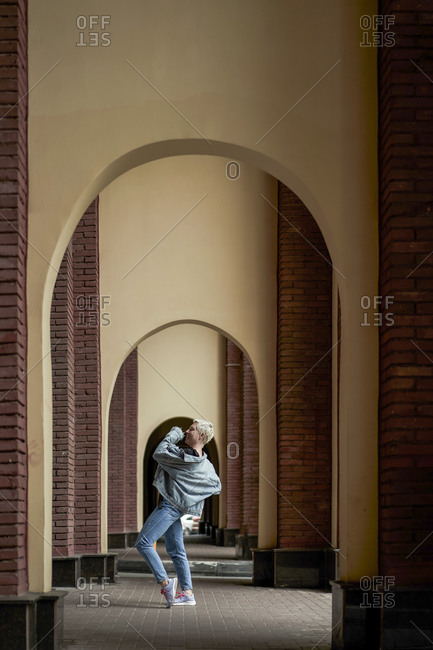Talented female dancer in denim clothes performing in arched walkway in city and looking away