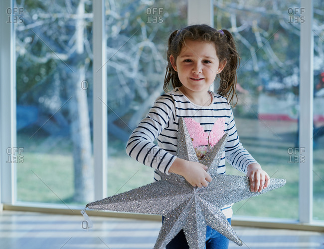 Smiling little girl with ponytails dressed in casual clothes holding silver star shaped Christmas decoration while standing against window at home