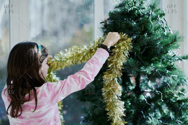 Back view of little girl in casual clothes hanging shiny yellow tinsel om artificial green tree while decorating room for Christmas celebration at home