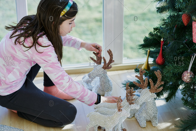 High angle side view of preteen girl arranging festive silver toy deer under decorated Christmas tree at home