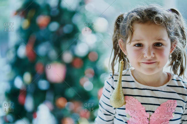 Cute little girl in casual clothes with ponytails and golden Christmas toy hanging on ear looking at camera while standing against shiny Xmas tree