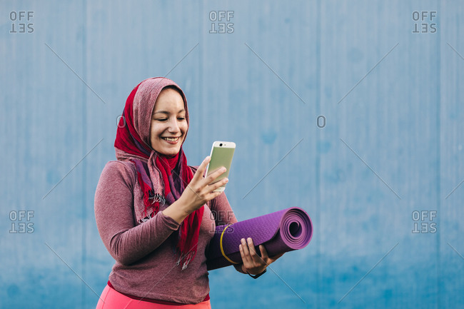 Content Arab woman in hijab and sportswear standing with twisted mat on street and browsing mobile phone before training