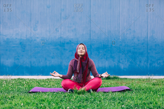 Serene Arab female in sportswear and hijab sitting on mat on lotus pose with eyes closed in park and doing yoga in Padmasana with closed eyes