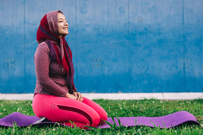 Side view of serene Arab female in sportswear and hijab sitting on mat on Hero pose with eyes closed in park and doing yoga in Padmasana