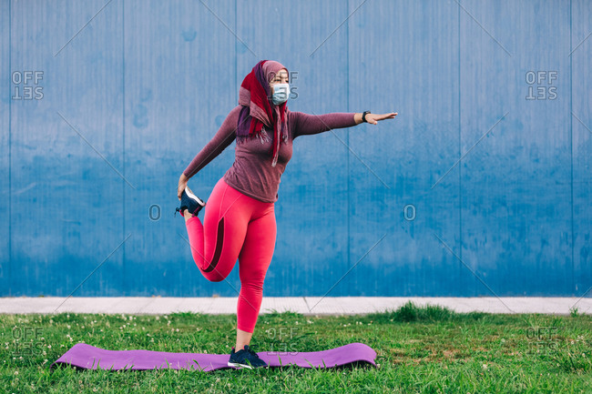 Arab female athlete in medical mask and hijab standing on mat and stretching legs while warming up before workout