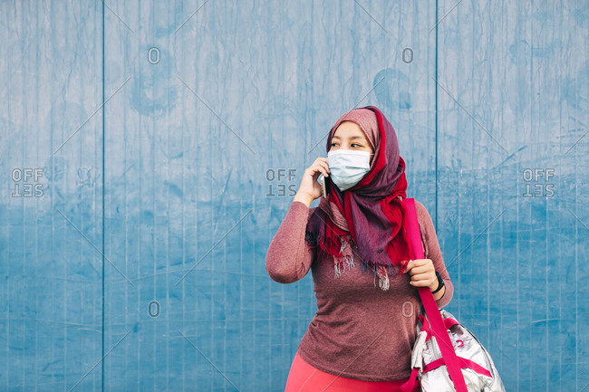 Arab female in sportswear and medical mask standing near building in city speaking on mobile phone after training while looking away