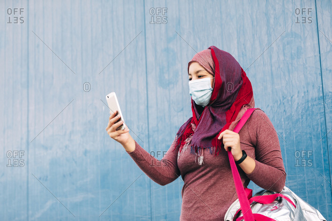 Arab female in sportswear and medical mask standing near building in city and browsing cellphone after training while looking at camera