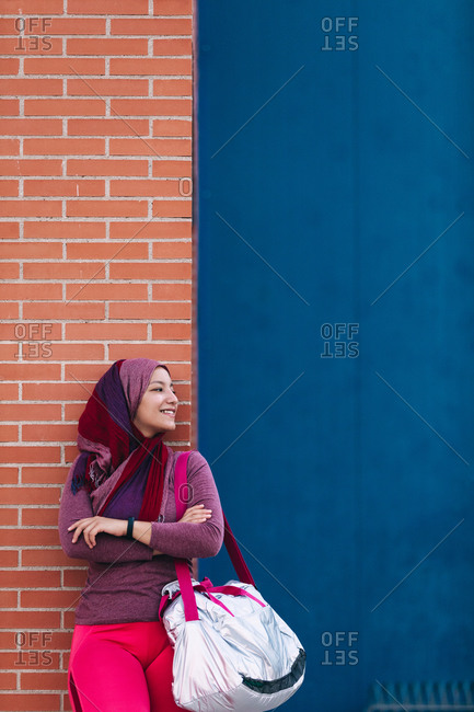 Content Arab female athlete in hijab standing with sports bag near building and relaxing after training while looking away