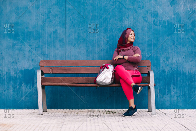 Content Arab female athlete in hijab sitting on a bench on the street with sports bag near building and relaxing after training while looking away