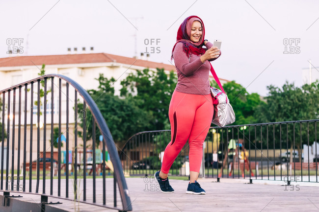 Side view of happy Arab sportswoman in hijab walking on metal railing on street and chatting on social media after training