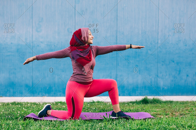Side view of Arab female in active wear and hijab practicing yoga in Crescent Lunge pose on mat in park