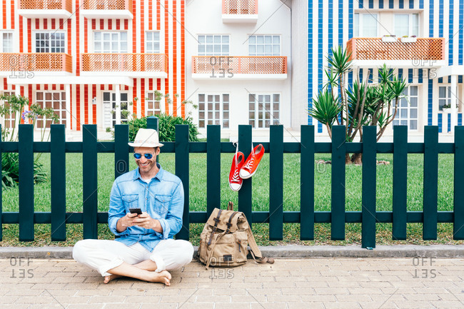 Full body smiling trendy man with backpack resting on sidewalk of Costa Nova with sneakers on fence and using phone