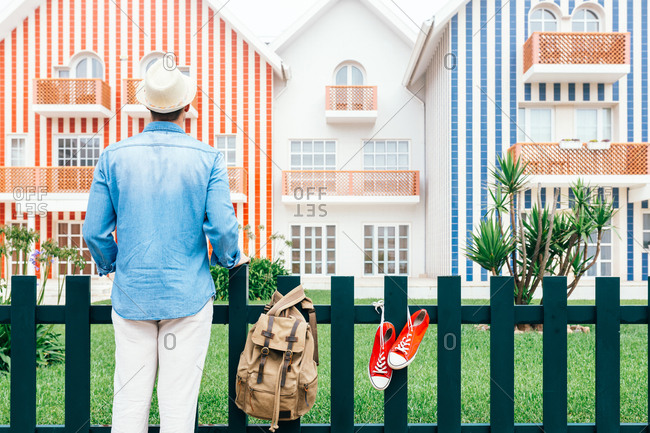 Back view of man standing at fence on Costa Nova with sneakers and backpack on fence and looking at colorful striped houses